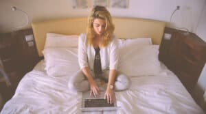 woman sitting on bed with laptop-starting an online business