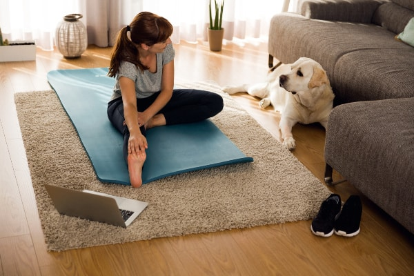 lady sitting on yoga mat with dog- best bodyweight exercises
