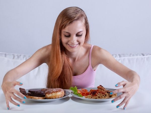 woman with food plates-eating before bed is bad for you