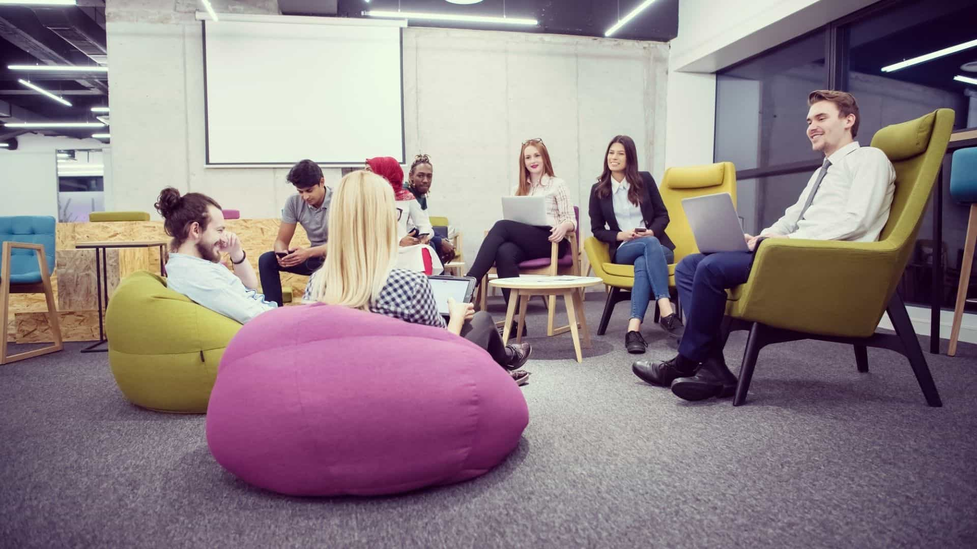 people at work sitting in a meeting in chairs