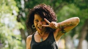 happy woman with peace sign-how to change your life at 50