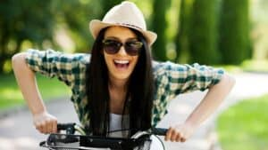smiliing woman on bike-how to live a happier life article