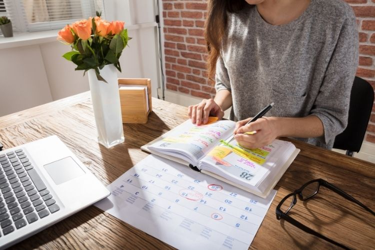 woman sitting at desk with a day planner-getting out of rock bottom